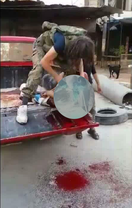 A blurred screenshot from the video of the beheading in Handarat [19/7/2016]